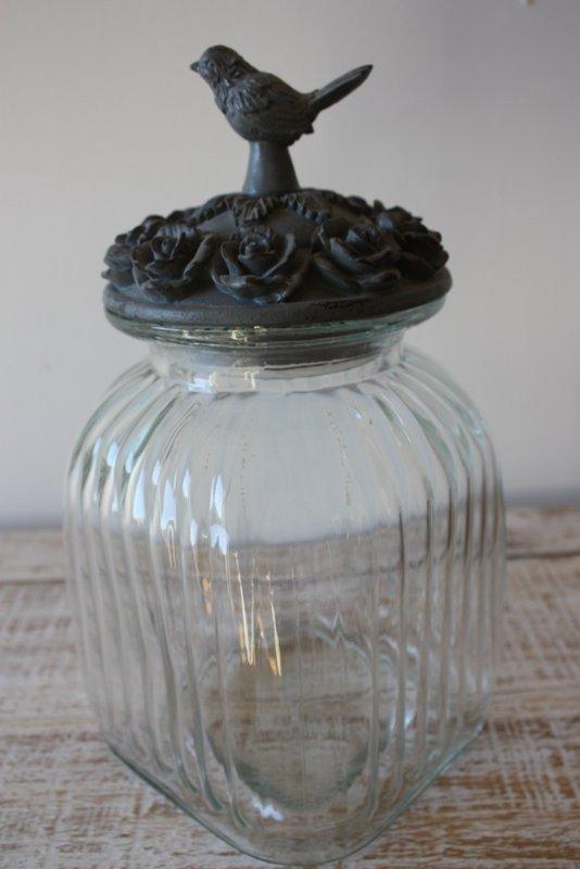 Bocal en verre avec oiseau pose sur un couvercle gris